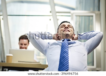 caucasian business person sitting in office thinking daydreaming hands behind head. - stock photo