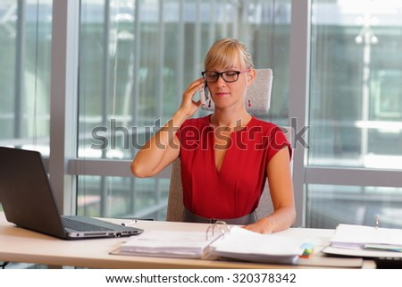 caucasian business woman in eyeglasses on phone in her office - stock photo