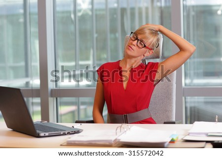 caucasian business woman in eyeglasses relaxing neck,stretching arms - short break for exercise on chair  in office - stock photo