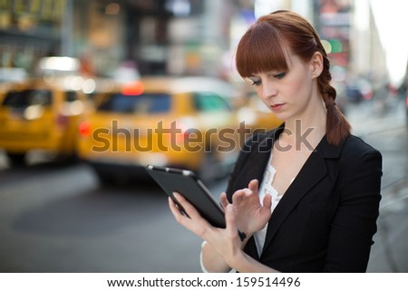 Caucasian business woman in New York City using ipad tablet pc computer reading ebook - stock photo