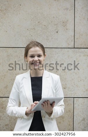 Caucasian Business woman using digital tablet computer, leaning against a marble wall. - stock photo