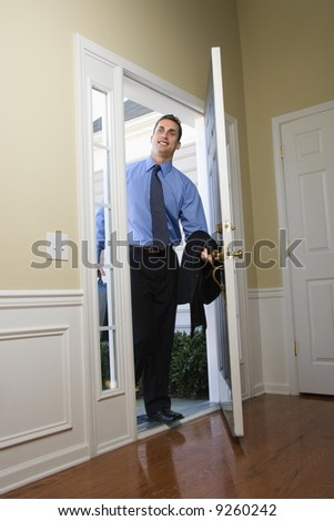 Caucasian businessman   at open door with briefcase. - stock photo