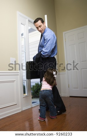 Caucasian businessman   at open door with briefcase with daughter tugging on his leg. - stock photo