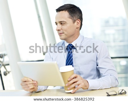 caucasian businessman holding tablet computer and coffee cup looking away thinking in office. - stock photo