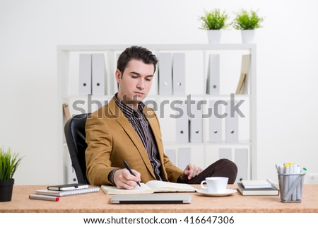 Caucasian businessman in brown jacket sitting at office desk and reflecting something in journal - stock photo