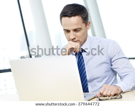 caucasian businessman in shirt and tie looking at laptop computer and thinking in office. - stock photo