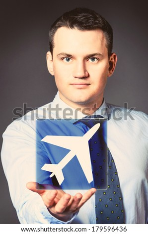 caucasian businessman is holding airplane icon in hands - stock photo