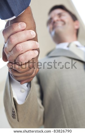 Caucasian businessman or man shaking hands with an African American colleague doing a business deal