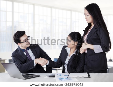 Caucasian businessman shaking hands with his partner in a business meeting at workplace - stock photo