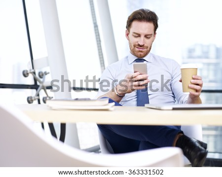caucasian businessman sitting at desk looking at mobile phone holding cup of coffee in office. - stock photo