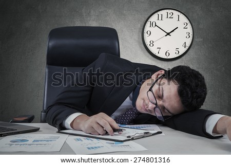 Caucasian businessman sleeping on the tablet with a clock on the wall, shot at workplace - stock photo