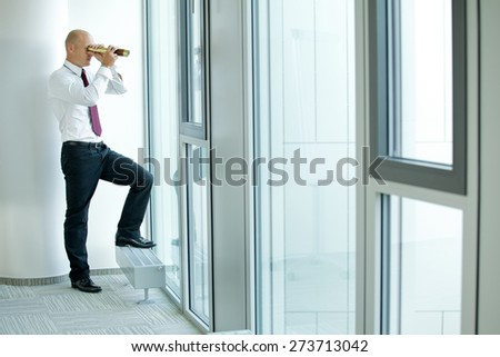 caucasian businessman spying using telescope thru office window - stock photo