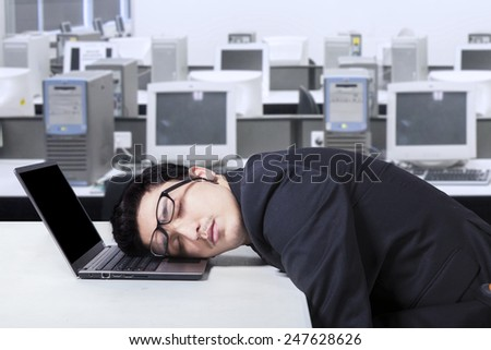 Caucasian businessman wearing formal suit and sleeping on his laptop in the workplace - stock photo
