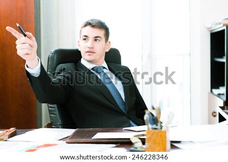 caucasian businessman while sitting at his desk in the office - stock photo