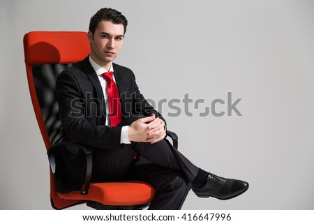 Caucasian businessman with crossed hands and legs sitting on red swivel chair - stock photo