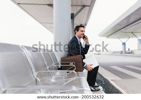 Caucasian businessperson calling on the phone while sitting at the bus stop in the airport