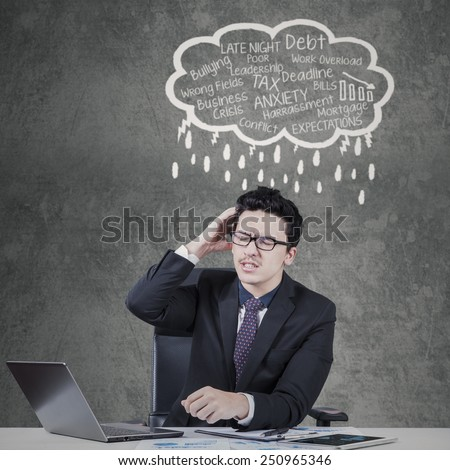 Caucasian businessperson getting headache thinking many job problems while scratching his head - stock photo