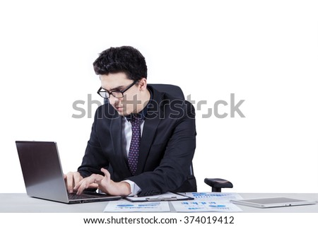 Caucasian businessperson typing on the laptop computer with paperwork on the table, isolated on white background - stock photo