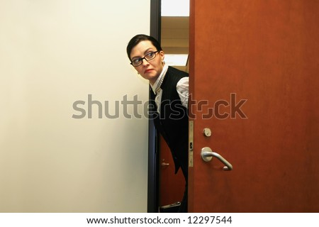 Caucasian businesswoman furtively peeking through a doorway - stock photo