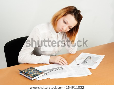 caucasian businesswoman sitting at desk in casual clothes and analyzing sales statistics - stock photo