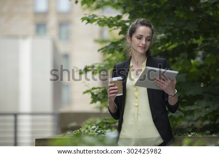 Caucasian Businesswoman using digital tablet computer. Business woman standing outside in modern city. - stock photo