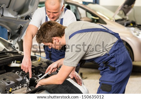 Caucasian car mechanics working together in garage - stock photo