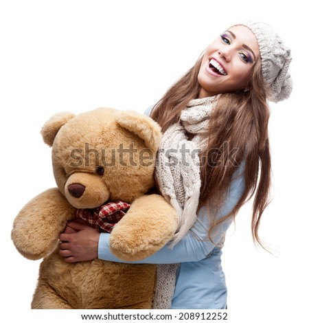 caucasian casual smiling young woman in winter clothing holding big soft Teddy Bear. isolated on white - stock photo