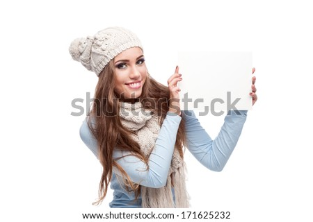 caucasian casual smiling young woman in winter clothing holding sign. isolated on white