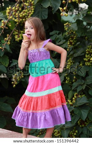 Caucasian charming little girl eats ice-cream smiling and laughing in the park on a summer background of green trees - stock photo