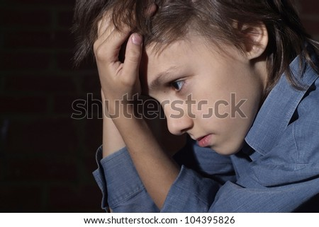 Caucasian child frustrated sitting in a deserted place - stock photo