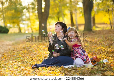 caucasian child girl and mother blowing soap bubbles outdoor at autumn sunset - happy carefree childhood - stock photo