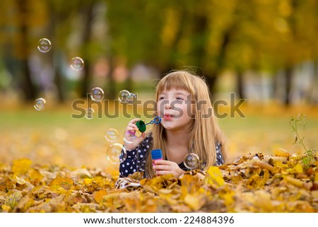 caucasian child girl blowing soap bubbles outdoor at autumn sunset - happy carefree childhood - stock photo