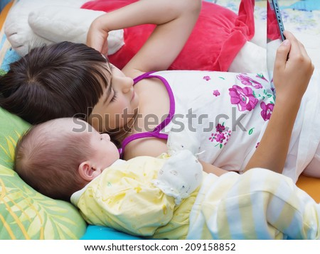 Caucasian child sister and baby brother lying together at home with tablet pc - stock photo