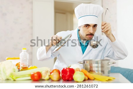 Caucasian  cook tasting soup with ladle from pan in kitchen - stock photo