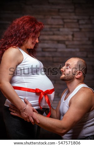 Caucasian couple expecting baby in front of the brick wall