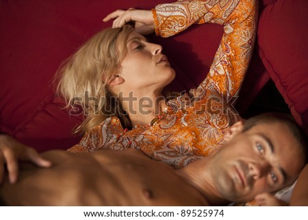 Caucasian couple relaxing on a sofa. - stock photo