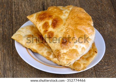 Caucasian cuisine - Cheburek pie on the wood background