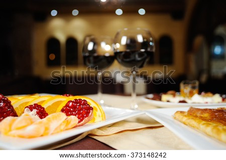 Caucasian cuisine. glasses of red wine and snacks on a table - stock photo