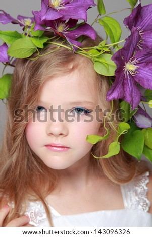 Caucasian cute little girl with beautiful hairstyle with fresh bright clematis smiles and poses for the camera - stock photo