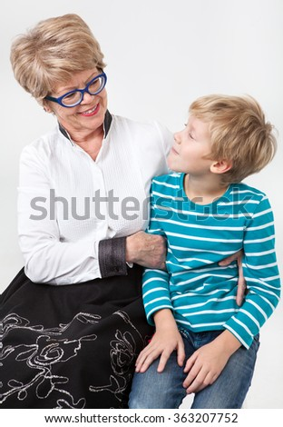 Caucasian elderly woman and young boy together looking each other, portrait on a gray background - stock photo