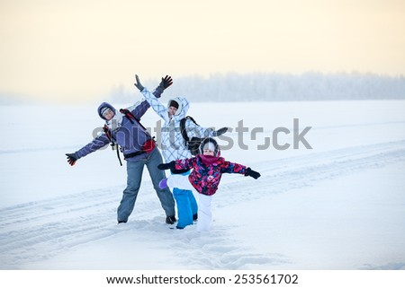 Caucasian family from three women standing with raising hands on frozen lake, winter hiking - stock photo