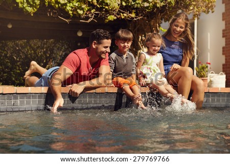 Caucasian family having fun by their swimming pool. Happy young family splashing water with hands and legs while sitting on edge of swimming pool. Kids with parents playing outdoors. - stock photo
