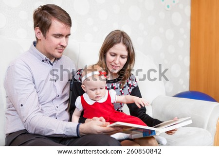Caucasian family reading the book sitting on sofa - stock photo