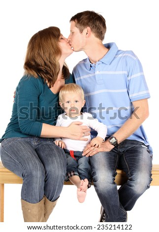 Caucasian family with mom dad and baby boy. They are all wearing denim jeans and sitting on a wooden bench. The parents are kissing each other. Image is isolated on a white background. - stock photo