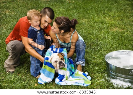 Caucasian family with toddler son drying English Bulldog with towel after a bath outdoors. - stock photo