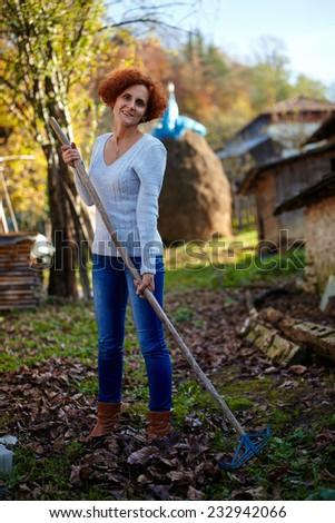 Caucasian farmer woman with a rake cleaning her garden of fallen leaves - stock photo