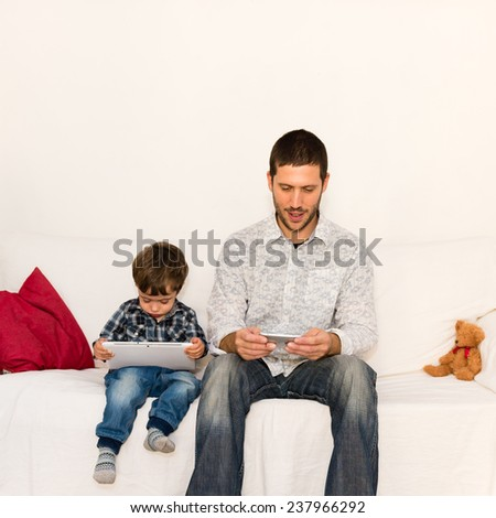Caucasian father and son playing with tablet on a white sofa with a red pillow and a bear toy - stock photo