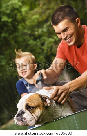 Caucasian father and toddler son giving  English Bulldog a bath outdoors. - stock photo