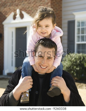 Caucasian father carrying daughter on shoulders. - stock photo