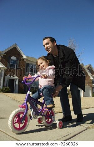 Caucasian father helping daughter ride bicycle. - stock photo